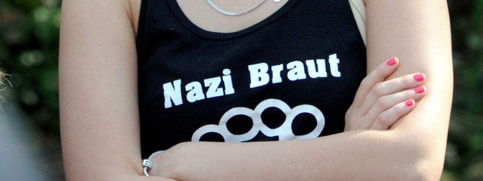 """Eine weibliche Teilnehmerin trägt bei einer Veranstaltung der NPD ein T-Shirt mit der Aufschrift """"Nazi Braut""""."""