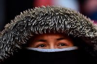 An Arsenal fan wrapped against the cold waits for kick off of the English League Cup final football match between Manchester City and Arsenal at Wembley stadium in north London on February 25, 2018. / AFP PHOTO / Glyn KIRK / RESTRICTED TO EDITORIAL USE. No use with unauthorized audio, video, data, fixture lists, club/league logos or 'live' services. Online in-match use limited to 75 images, no video emulation. No use in betting, games or single club/league/player publications.  /