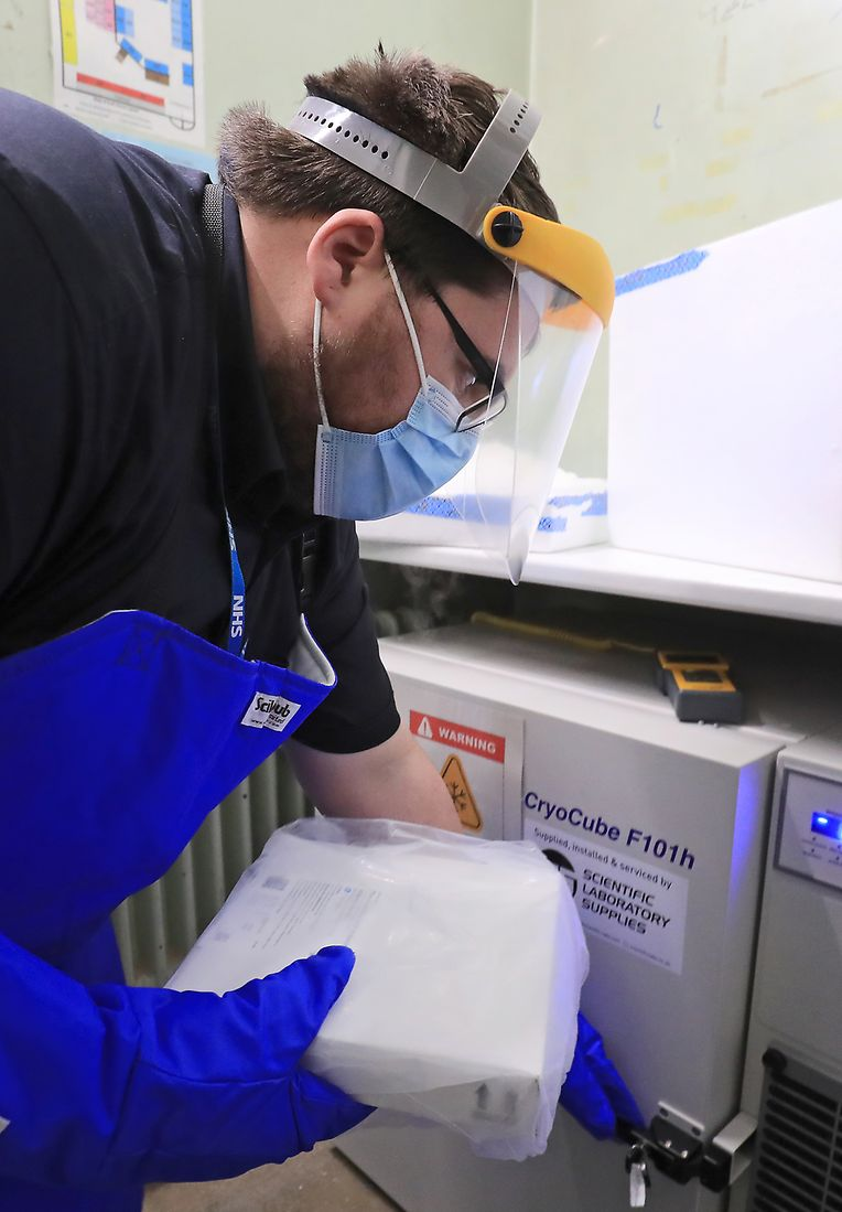 Ein Apothekentechniker des Gesundheitsdienstes von Croydon legt im Universitätskrankenhaus Croydon die erste Charge der Covid-19-Impfungen, die in das Gebiet geliefert werden sollen, ins Ultratiefkühlgerät.