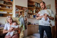 Phillip L�hl (R) holds his new born baby Paula as Frauke L�hl (L), Phillip's mother, takes care of Paula's twin sister Maya at their temporary accommodation in Auckland Park, Johannesburg, on April 14, 2021. - Paula and Maya are daughters of a gay couple -- a Namibian and a Mexican -- and were born through surrogacy by a South African woman. Efforts to take them to Windhoek since their birth on March 13, 2021, have hit a snag, forcing the parents - Phillip L�hl, 38, and his partner Guillermo Delgado, 36,  to resort to the courts. Their parents are now pinning hopes on a Namibian High Court ruling scheduled for April 19, 2021, to at least allow the infants to secure temporary documents to travel to Windhoek and join Delgado and their two-year-old brother Yona. (Photo by LUCA SOLA / AFP)