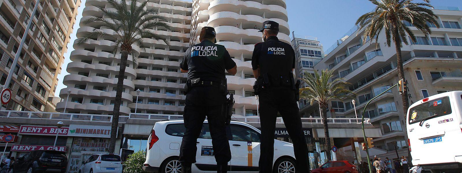 Zwei Polizisten stehen im Einsatz vor dem Hotel in Palma de Mallorca, in dem mehr als 200 Schüler in Corona-Zwangsquarantäne gesetzt wurden.