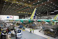 (FILES) In this file photo taken on March 27, 2019 Employees work on Boeing 737 MAX airplanes at the Boeing Renton Factory in Renton, Washington. - Boeing could on December 16, 2019 announce whether to further cut or suspend production of its grounded 737 MAX plane, The Wall Street Journal reported on December 15, 2019. (Photo by Jason Redmond / AFP)