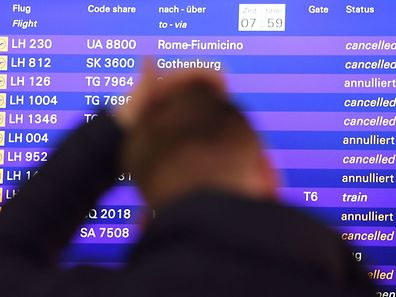 A flight passenger stands in front of a board displaying cancelled flights of German airline Lufthansa on November 25, 2016