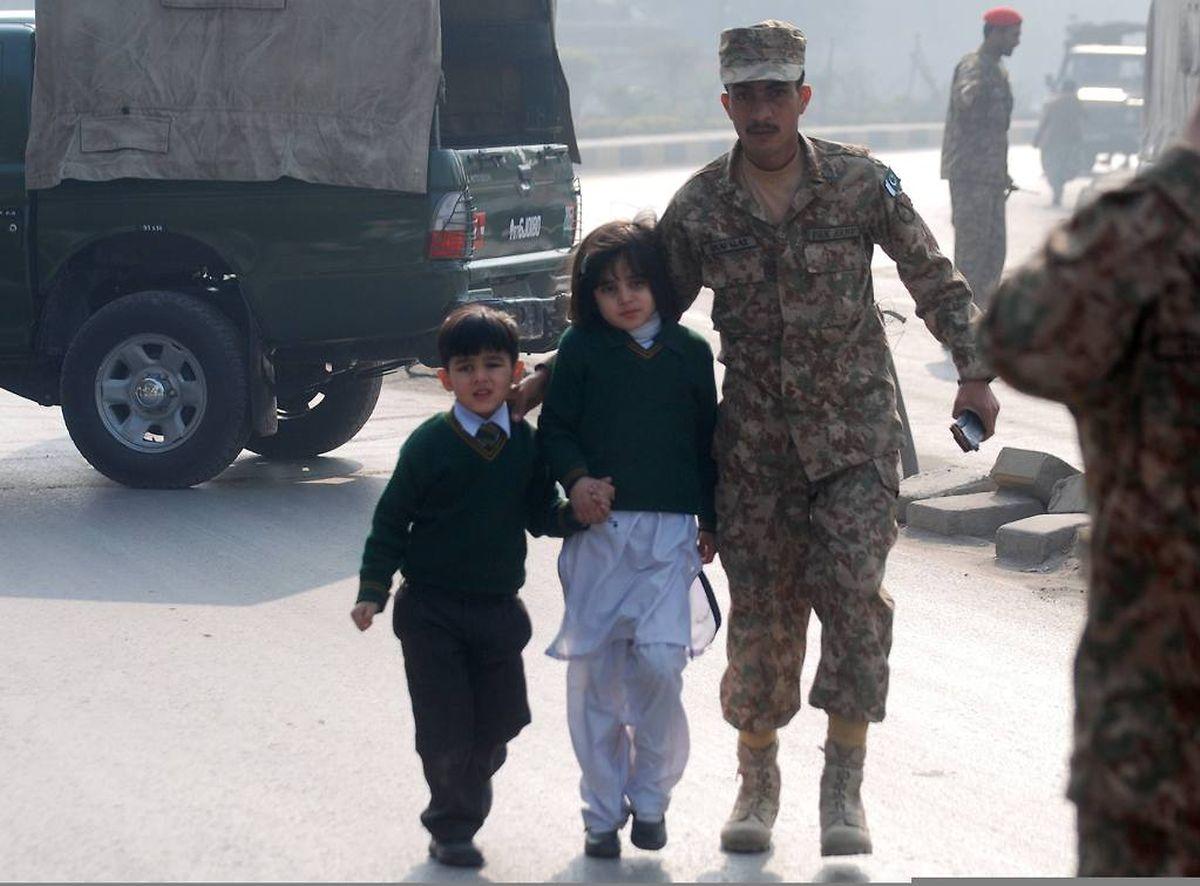 Soldaten bringen gerettete Schüler in Sicherheit.