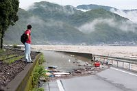 A man looks at the overflowing kuma river caused by heavy rain in Yatsushiro, Kumamoto prefecture on July 4, 2020. - Some 75,000 people were ordered to evacuate in western Japan on July 4 as record heavy rain triggered floods and landslides, local media and officials said. The nation's weather agency issued the highest level of heavy rain warnings to Kumamoto and Kagoshima on Kyushu island. (Photo by STR / JIJI PRESS / AFP) / Japan OUT