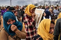 TOPSHOT - Mourners attend the funeral of civilians and fighters, who died during attacks by Turkish-led forces on the border town of Ras al-Ain, in a cemetary in Tal Tamr, near the Syrian Kurdish town of Ras al-Ain, October 19, 2019. - Turkish and Kurdish leaders accused each other of violating a US-brokered truce in northeastern Syria even as it appeared to be taking hold on its second day Saturday. (Photo by Delil SOULEIMAN / AFP)