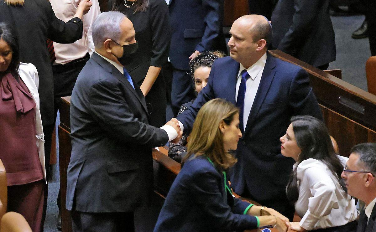 Israels scheidender Premierminister Benjamin Netanyahu schüttelt seinem Nachfolger Naftali Bennett die Hand.
