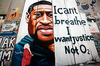 "TOPSHOT - A woman looks at a mural showing the face of George Floyd, an unarmed black man who died after a white policeman knelt on his neck during an arrest in the US, painted on a section of Israel's controversial separation barrier in the city of Bethlehem in the occupied West Bank on June 10, 2020, with text reading ""I can't breathe, I want justice not O2"". (Photo by Musa Al SHAER / AFP)"