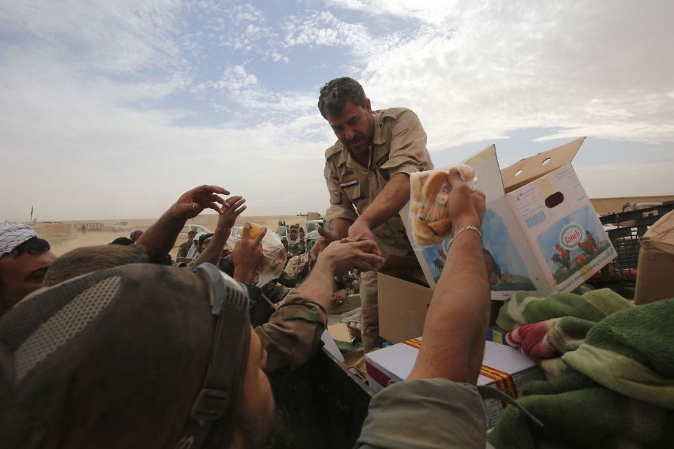 Iraqi forces distribute food as they enter the village of Abu Shuwayhah, south of jihadist-held Mosul, on November 1, 2016