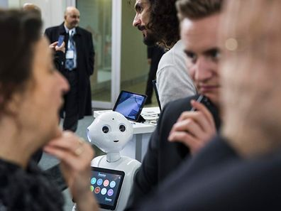 A robot looks at visitors at the Soft Bank robotics stand at the Cebit technology fair in Hannover on March 20, 2017.   The Digital Business fair CEBIT in Hanover with Japan as partner country runs from March 20 until March 24. / AFP PHOTO / Odd ANDERSEN