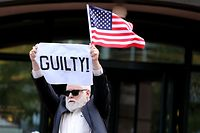 ALEXANDRIA, VA - AUGUST 21: A demonstrator holds up a sign and flag after leaving the Albert V. Bryan U.S. Courthouse after the jury announced verdicts in the trial for former Trump campaign manager Paul Manafort's trial August 21, 2018 in Alexandria, Virginia. Manafort was found guilty on at least one count as part of special counsel Robert Mueller's investigation into Russian interference in the 2016 presidential election.   Chip Somodevilla/Getty Images/AFP == FOR NEWSPAPERS, INTERNET, TELCOS & TELEVISION USE ONLY ==