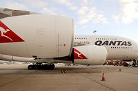 """(FILES) This file picture taken on August 11, 2011 shows a Qantas A380 Airbus on the tarmac at Tullamarine Airport in Melbourne, Australia.  Qantas removed one of its Airbus A380 superjumbos from service on February 8, 2012 after discovering """"minor cracks"""" in its wings, but said that there was no risk to flight safety.  AFP PHOTO / FILES / William WEST"""