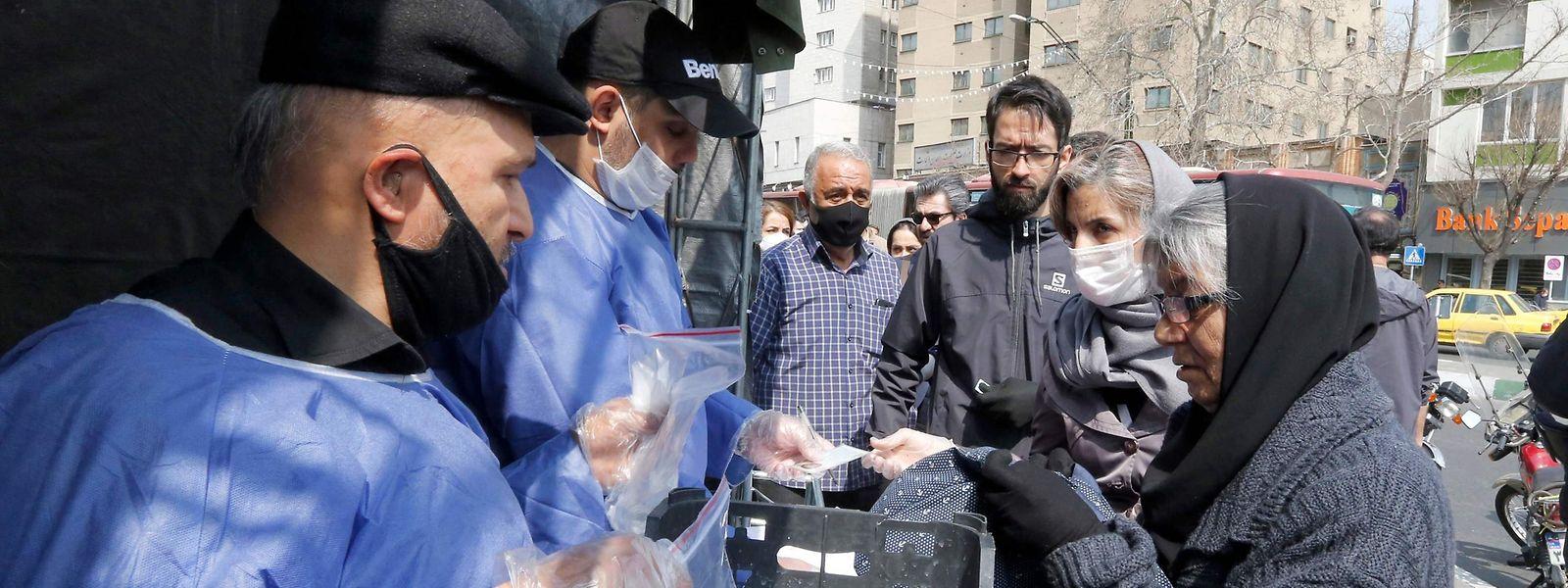 Vor einer Metrostation in Teheran werden Pakete mit Hinweisen zu Vorsichtsmaßnahmen verteilt.