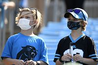 CHARLOTTE, NORTH CAROLINA - SEPTEMBER 12: Carolina Panthers fans look on while wearing masks prior to the game against the New York Jets at Bank of America Stadium on September 12, 2021 in Charlotte, North Carolina.   Mike Comer/Getty Images/AFP == FOR NEWSPAPERS, INTERNET, TELCOS & TELEVISION USE ONLY ==