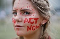 """A climate activists has """"Act Now"""" written on her face as she joins student and youth activists outside the Houses of Parliament in London on May 24, 2019 to demand action to tackle climate change. (Photo by Tolga Akmen / AFP)"""
