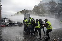 "(FILES) In this file photo taken on November 24, 2018 Yellow vest (Gilets jaunes) protestors stand as a water canon sprays on the Champs Elysees in Paris, during a protest against rising oil prices and living costs. - On November 17, 2018, 282,000 people according to the authorities, responded to a Facebook call, yellow vest on their backs, outside any political or trade union framework, and invested hundreds of roundabouts, symbols of the peri-urban France. The movement, born after a contested planned fuel tax, had shaken power for months and is now looking for other ways to perpetuate a new social movement, marked by the denunciation of ""police violence"". (Photo by Lucas BARIOULET / AFP)"