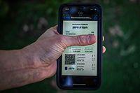 """ARCHIV - 26.02.2021, Israel, Tel Aviv: Ein israelischer Mann hält ein Smartphone in der Hand, auf dem der sogenannte """"Grüne Pass"""" abgebildet ist. In einem Versuch, aus den Corona-Maßnahmen zur Normalität zurückzukehren, hat die israelische Regierung damit begonnen, Zertifikate an Menschen auszugeben, die vollständig geimpft sind. Der """"Grüne Pass"""" wird benötigt, um bestimmte Orte zu betreten und an bestimmten Aktivitäten teilzunehmen. (Zu dpa """"Fußballfans kehren in Israels Stadien zurück - Impfung ist aber nötig"""") Foto: Ilia Yefimovich/dpa +++ dpa-Bildfunk +++"""
