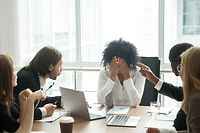 Rude diverse colleagues humiliating offending stressed upset young african woman leader suffering from gender racial discrimination during meeting or feeling exhausted tired of responsibility at work