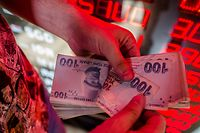 TOPSHOT - A money changer counts Turkish lira banknotes at a currency exchange office in Istanbul, on August 8, 2018. - The Turkish lira on August 1 slumped to record lows of 5,0 against the dollar as the US hit Turkey's justice and interior ministers with sanctions over the case of an American pastor on trial for terror-related charges. (Photo by Yasin AKGUL / AFP)