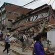 Nepalese people walk past a collapsed bullding in Kathmandu after an earthquake on April 25, 2015. A massive 7.8 magnitude earthquake killed hundreds of people April 25 as it ripped through large parts of Nepal, toppling office blocks and towers in Kathmandu and triggering a deadly avalanche that hit Everest base camp. AFP PHOTO / PRAKASH MATHEMA