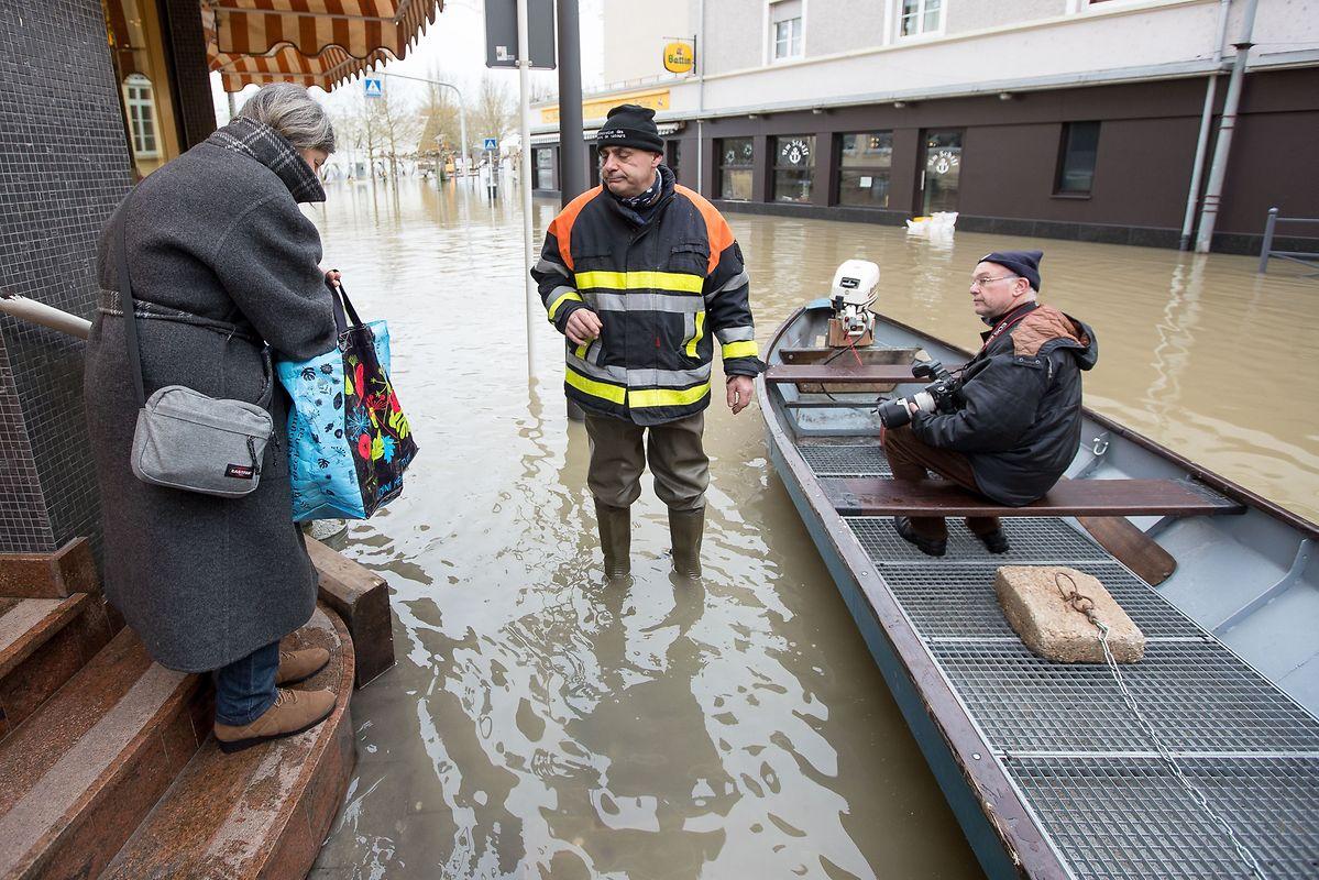 Die Feuerwehr hilft wo sie kann. Der Sohn dieser Dame ist eingeschlossen und hat nichts zu essen. Die Feuerwehr bringt ihm die Tüten voll mit Essen mit dem Boot.