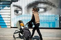 Jose, 45, pushes her son Pol's stroller past a mural depicting a person wearing a face mask, on April 26, 2020, in Barcelona, during a national lockdown to prevent the spread of the COVID-19 disease. - After six weeks stuck at home, Spain's children were being allowed out today to run, play or go for a walk as the government eased one of the world's toughest coronavirus lockdowns. Spain is one of the hardest hit countries, with a death toll running a more than 23,000 to put it behind only the United States and Italy despite stringent restrictions imposed from March 14, including keeping all children indoors. Today, with their scooters, tricycles or in prams, the children accompanied by their parents came out onto largely deserted streets. (Photo by Josep LAGO / AFP)