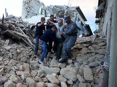 Residents and rescuers help a man among the rubble after a strong heartquake hit Amatrice