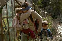 """HANDOUT - 13.02.2018, ---: Sandra Bullock mit Vivien Lyra Blair und Julian Edwards in einer Szene des Netflix-Horrorthrillers «Bird Box» (undatierte Filmszene). Wer hinschaut, stirbt. So lautet das Mantra im Netflix-Horror «Bird Box». Sandra Bullock spielt darin eine Mutter, die mit verbundenen Augen in einem dystopischen Amerika vor unsichtbaren Monstern flieht. (zu dpa """"Für Likes gegen die Wand - Über die Faszination von Online-Mutproben"""" vom 11.01.2019) Foto: Saeed Adyani/Netflix/dpa - ACHTUNG: Verwendung nur im Zusammenhang mit der Berichterstattung über das Streaming der Serie «Bird Box» und nur mit Urhebernennung +++ dpa-Bildfunk +++"""