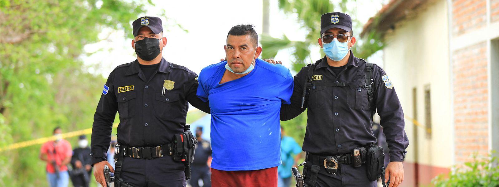 Der verdächtige Ex-Polizist wird von Beamten abgeführt.