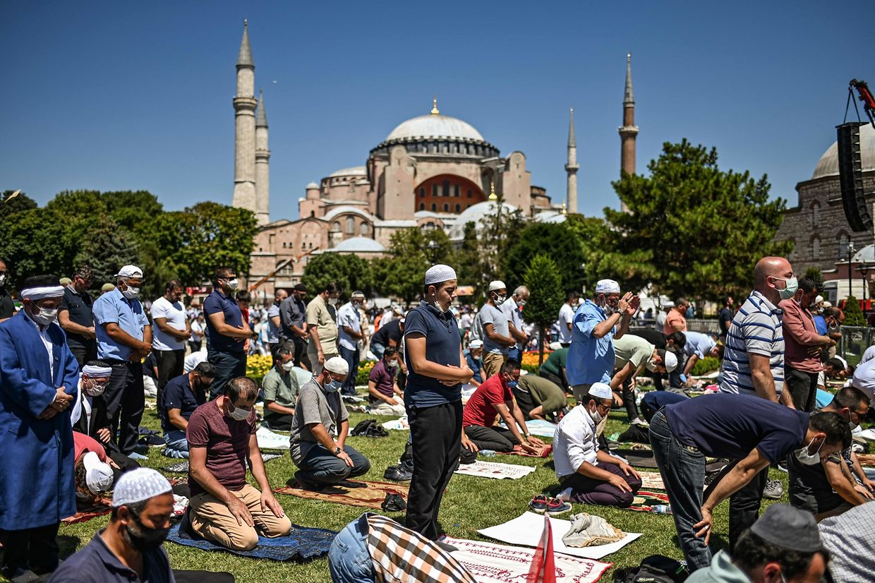 TOPSHOT - Men perform the Friday prayer on July 24, 2020 outside Hagia Sophia in Istanbul, the first muslim prayer held at the landmark since it was reconverted to a mosque despite international condemnation. - A top Turkish court revoked the sixth-century monument's status as a museum on July 10 and Turkish President then ordered the building to reopen for Muslim worship. The UNESCO World Heritage site in historic Istanbul was first built as a cathedral in the Christian Byzantine Empire but was converted into a mosque after the Ottoman conquest of Constantinople in 1453. (Photo by Ozan KOSE / AFP)