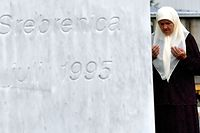 Bosnian Muslim woman Mejra Djogaz, 71, survivor of Srebrenica 1995 massacre, prays at the entrance of the Potocari memorial center near Srebrenica, where are her son's tombstones, Omer, 19, and Munib, 21, her two sons killed in the massive killing of Srebrenica during Bosnia's 1992-95 war, on July 3, 2020. - Eight thousands Muslim men and boys were killed by Serb forces in the eastern enclave towards the end of Bosnia's 1992-95 war, an atrocity deemed a genocide by international courts, whose remains were found in mass graves after the conflict, were buried a decade ago in the memorial centre where more than 6,600 victims of the victims lie. Another 237 have been laid to rest at other sites. But more than 1,000 people have never been found, an acute source of pain for survivors. (Photo by ELVIS BARUKCIC / AFP)