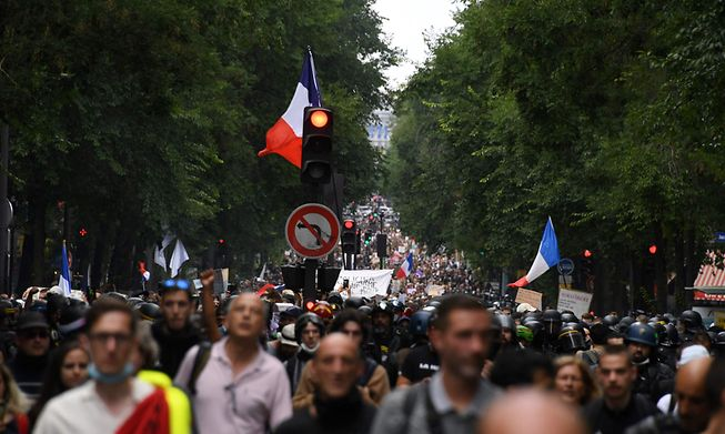 People take part in a demonstration part of a national day of protest against French legislation making a Covid-19 health pass compulsory to visit a cafe, board a plane or travel on an inter-city train, in Paris on July 31, 2021.