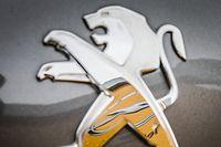 """ARCHIV - 06.03.2017, Hessen, Darmstadt: Ein Opel-Logo spiegelt sich am 06.03.2017 in Darmstadt (Hessen) vor einem Autohaus, das beide Marken führt, in einem Peugeot-Logo auf der Motohaube eines Fahrzeugs. (zu """"Opel-Mutter PSA und Fiat Chrysler bestätigen Fusionsgespräche"""") Foto: Frank Rumpenhorst/dpa +++ dpa-Bildfunk +++"""