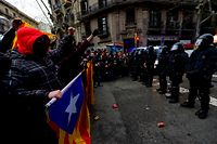 Protesters shout slogans opposite riot police blocking the road leading to the central government offices during a demonstration in Barcelona on March 25, 2018 after Catalonia's former president was arrested by German police. German police arrested Catalonia's deposed leader Carles Puigdemont on March 25, 2018, five months after he went into self-imposed exile in Belgium over his failed bid to break the region away from Spain.  / AFP PHOTO / LLUIS GENE