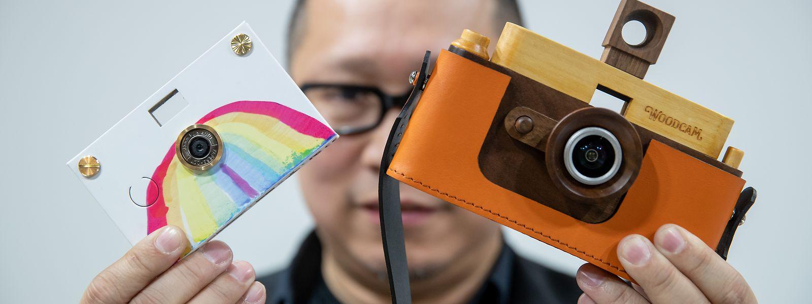 Es geht auch ohne Plastik: Jimmy Chen vom US-Unternehmen Father's Factory präsentiert auf der Spielwarenmesse Digitalkameras mit Holz- und Papiergehäuse.