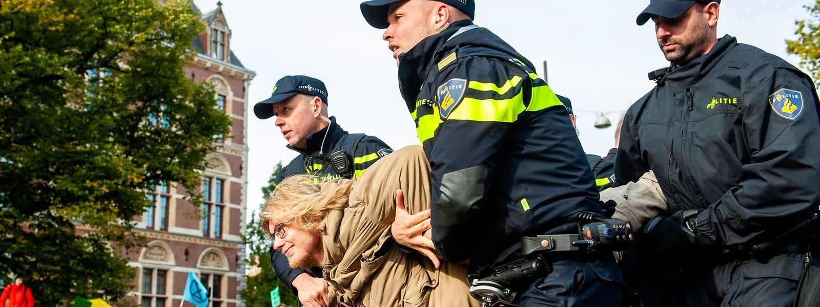 Eine Demonstrantin wird in Amsterdam von Polizisten aus einer Sitzblockade entfernt.