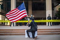 A demonstrator holding a US flag kneels in front of the Police at the Anaheim City Hall on June 1, 2020 in Anaheim, California, during a peaceful protest over the death of George Floyd. - Major US cities -- convulsed by protests, clashes with police and looting since the death in Minneapolis police custody of George Floyd a week ago -- braced Monday for another night of unrest. More than 40 cities have imposed curfews after consecutive nights of tension that included looting and the trashing of parked cars. (Photo by Apu GOMES / AFP)