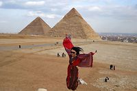 A tourist jumps as she has her picture taken at the Giza pyramids necropolis on the southwestern outskirts of the Egyptian capital Cairo on December 29, 2018, with the pyramids of Khafre (or Chephren, R) and Khufu (or Cheops, L) seen in the background. (Photo by MOHAMED EL-SHAHED / AFP)